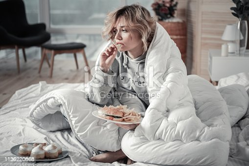 Burger and fries. Sad and lonely blonde-haired young woman eating burger and French fries in the bed