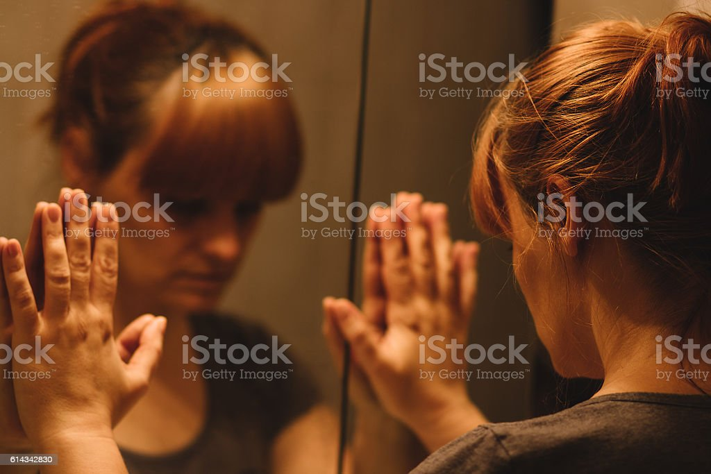 Sad and lonely woman looking at her reflection royalty-free stock photo