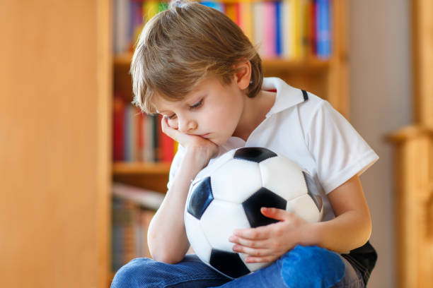 sad and not happy little kid with football about lost football or soccer game. child after watching match on tv - criança perdida imagens e fotografias de stock