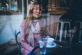Sad and pensive young woman sitting at cafe,