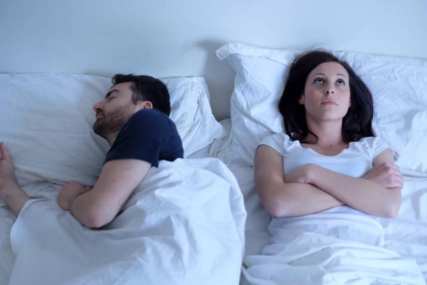 Üzgün ve düşünceli kadın kocası yatakta uyurken uyanık stok fotoğrafı