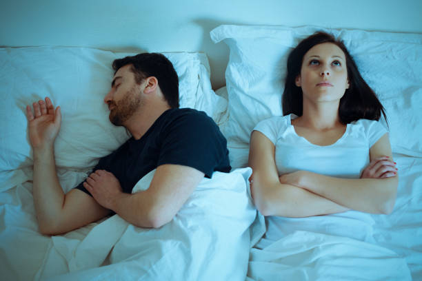 Sad and thoughtful woman awake while husband is sleeping in bed Sad and thoughtful woman awake while husband is sleeping in the bed couple in bed stock pictures, royalty-free photos & images