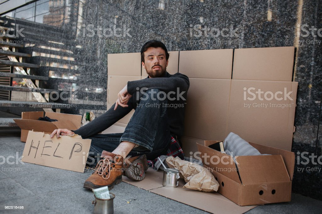 Sad and tired dark-haired man is sitting on the cardboard and holding another cardboard with the word help writing on it. He is looking aside. He is homeless - Royalty-free Adult Stock Photo