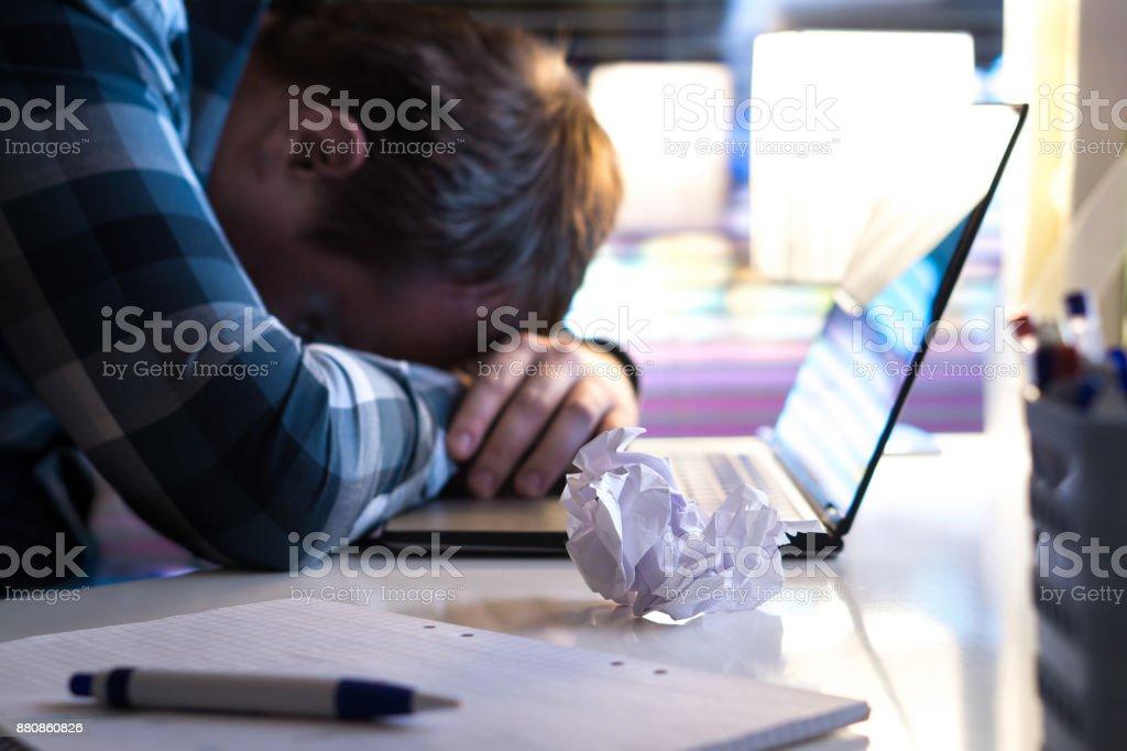 Hombre triste y cansado en oficina hogar negocio moderno en la noche. Desempleada demandante de empleo o empresario con papel rasgado y ordenador portátil en la mesa. - foto de stock