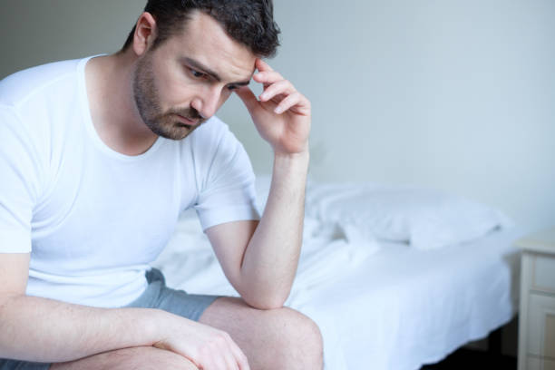 Sad and upset man waking up in the morning light Sad and upset man waking up in the morning light erectile dysfunction stock pictures, royalty-free photos & images