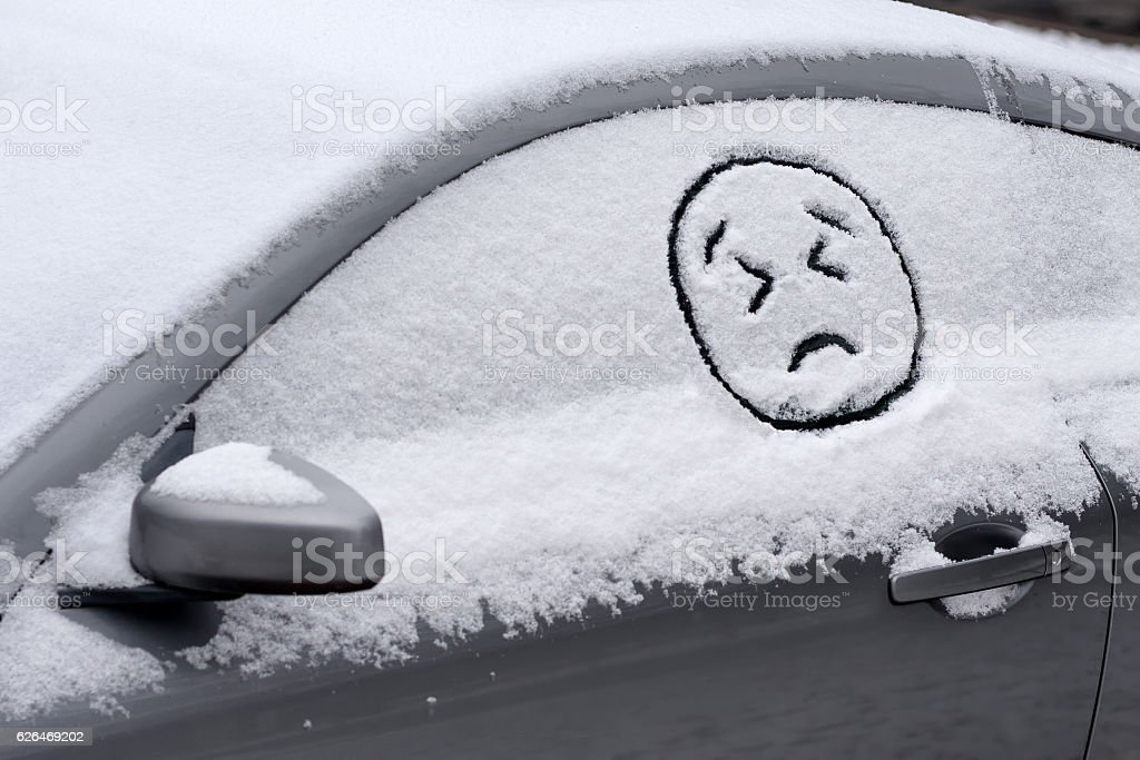 Sad Angry Face Emoji in Snow on Car stock photo