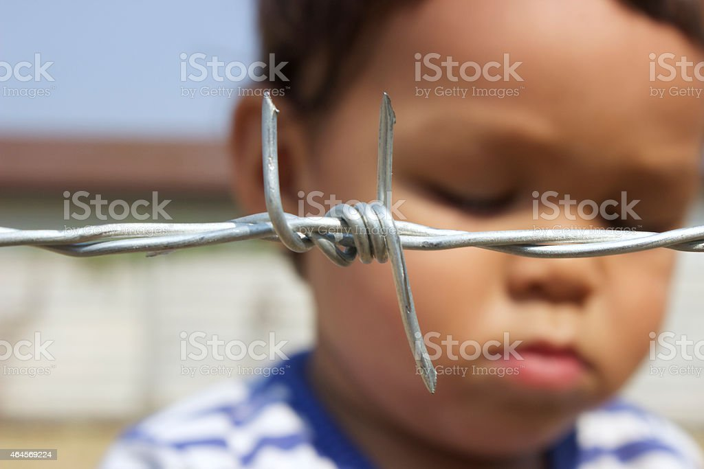 Sad Asian Boy Behind Barbed Wire stock photo
