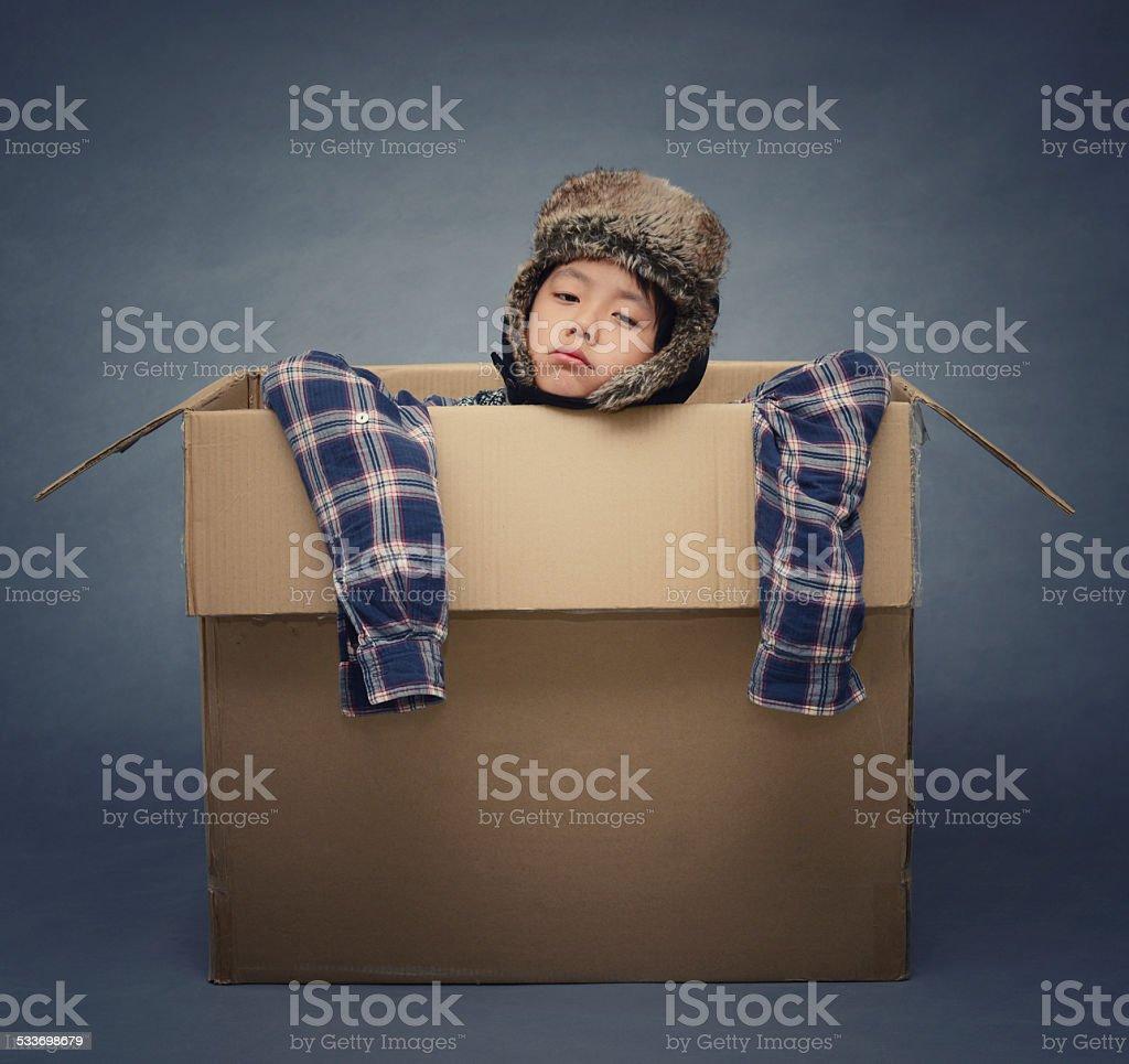 Sad Asian boy wearing winterhat inside cardboard box stock photo