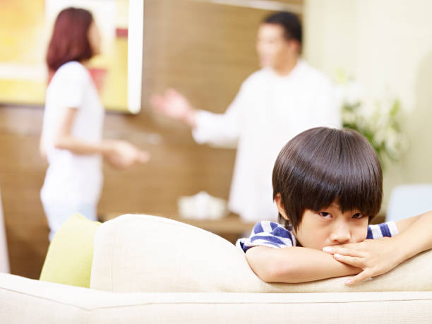sad asian child and quarreling parents asian child appears sad and unhappy while parents quarreling in the background. asian couple arguing stock pictures, royalty-free photos & images