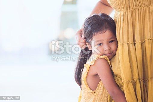 Sad asian child girl hugging her mother leg in vintage color tone
