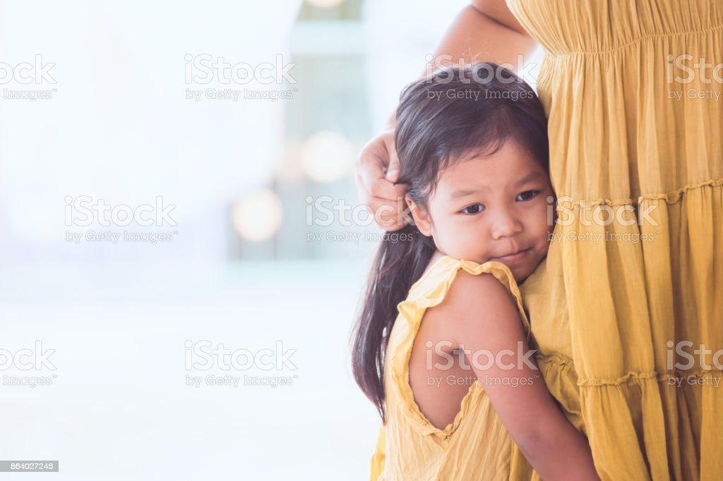 Sad asian child girl hugging her mother leg in vintage color tone stock photo