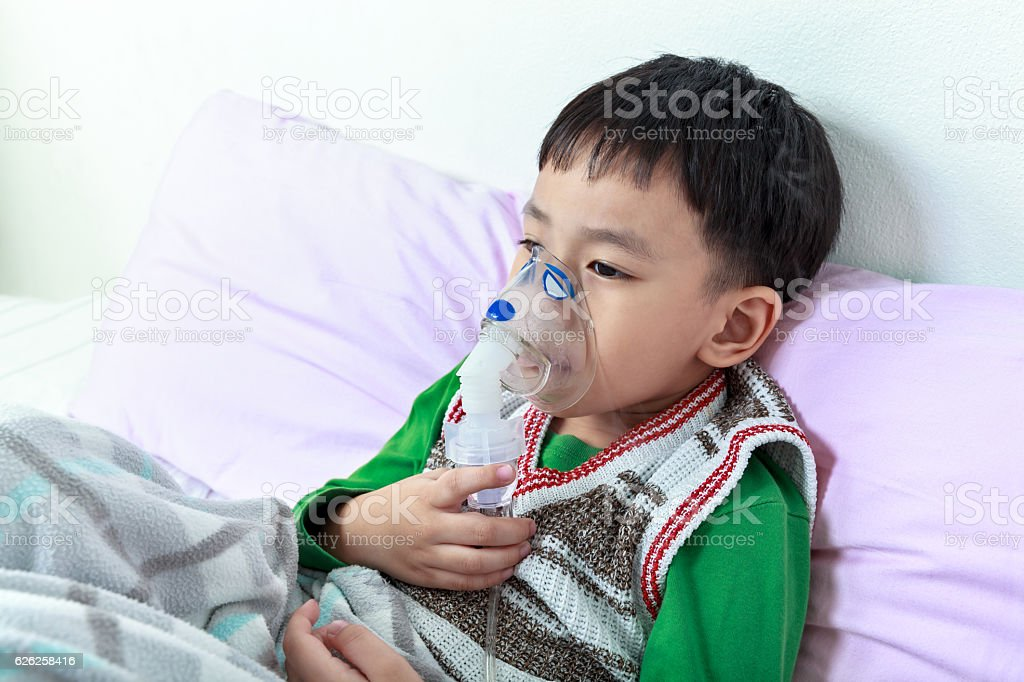 Sad asian child holds a mask vapor inhaler. stock photo