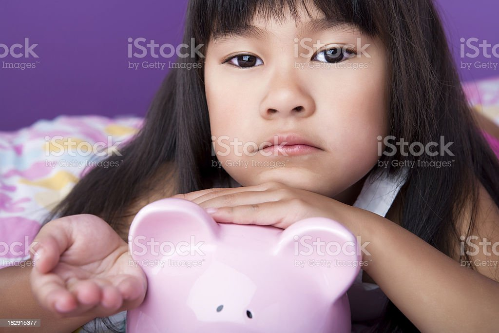 Sad asian girl holding piggy bank stock photo