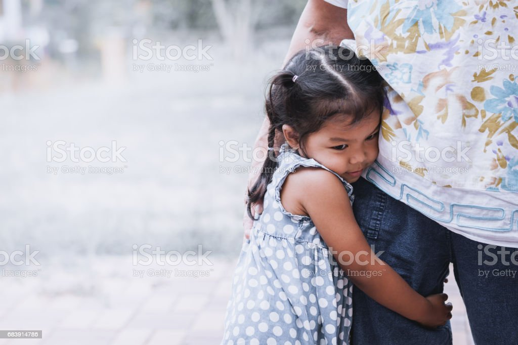 Sad asian little girl hugging her mother leg stock photo