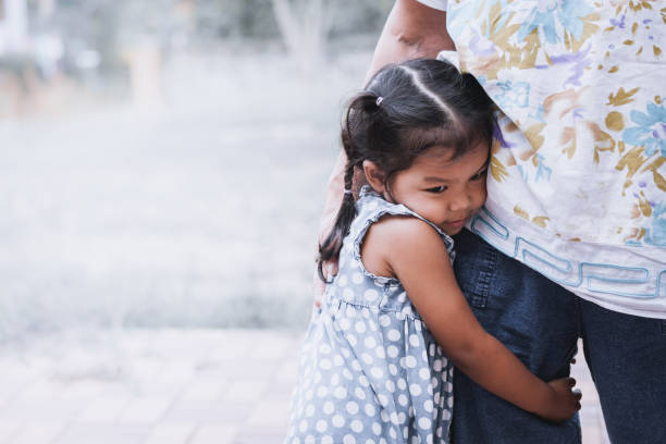 sad asian little girl hugging her mother leg - fear stock photos and pictures