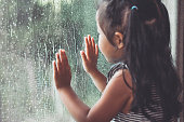 istock Sad asian little girl looking outside through the window in the rainy day 696110830