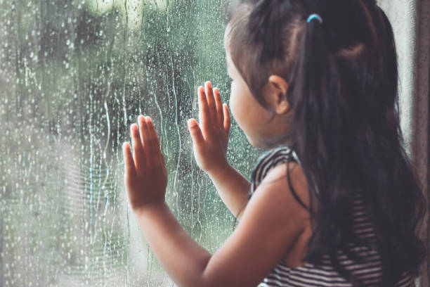 Sad asian little girl looking outside through the window in the rainy day stock photo