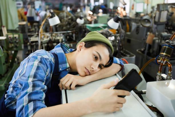 Sad attractive young woman worker in beanie hat being bored at workplace, she using smartphone and leaning on industrial equipment stock photo