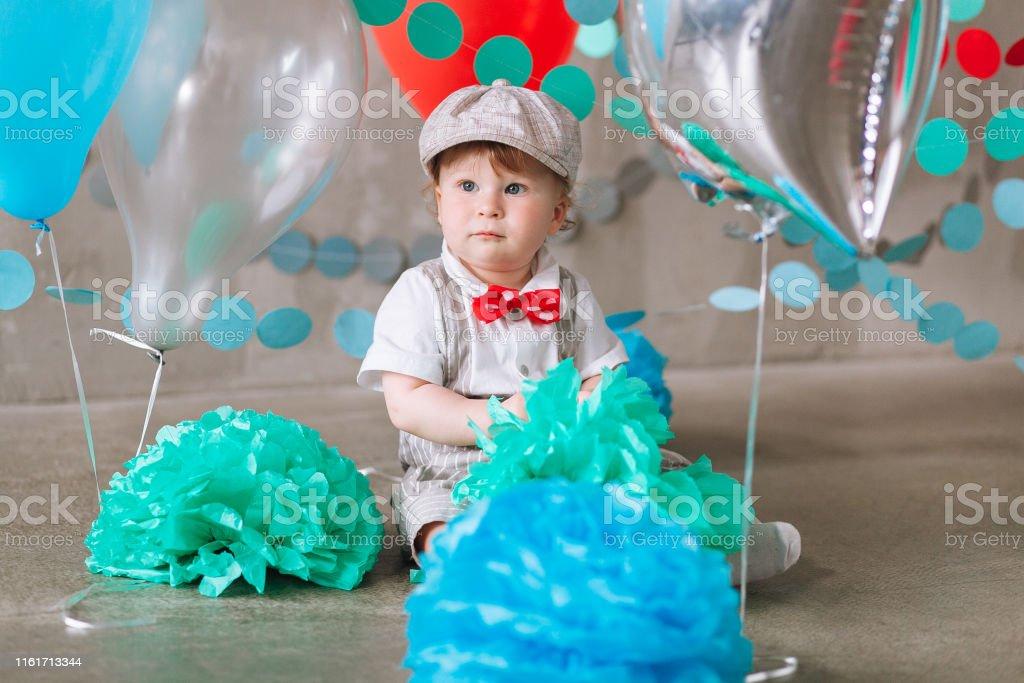 Happy baby boy celebrating first birthday. Kids birthday party...