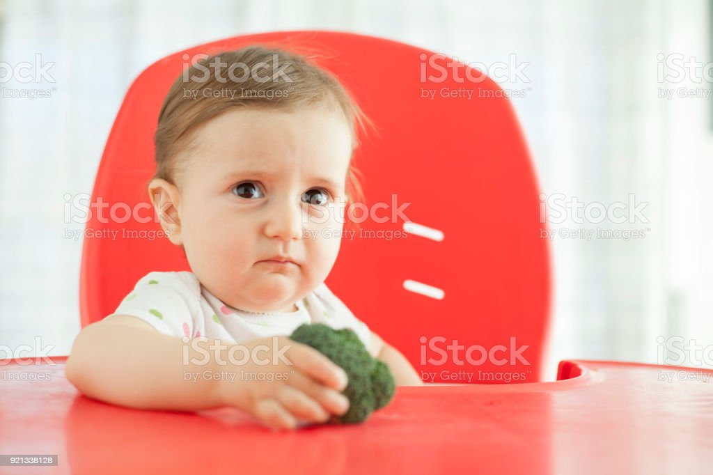 Sad baby doesn't want to eat broccoli stock photo