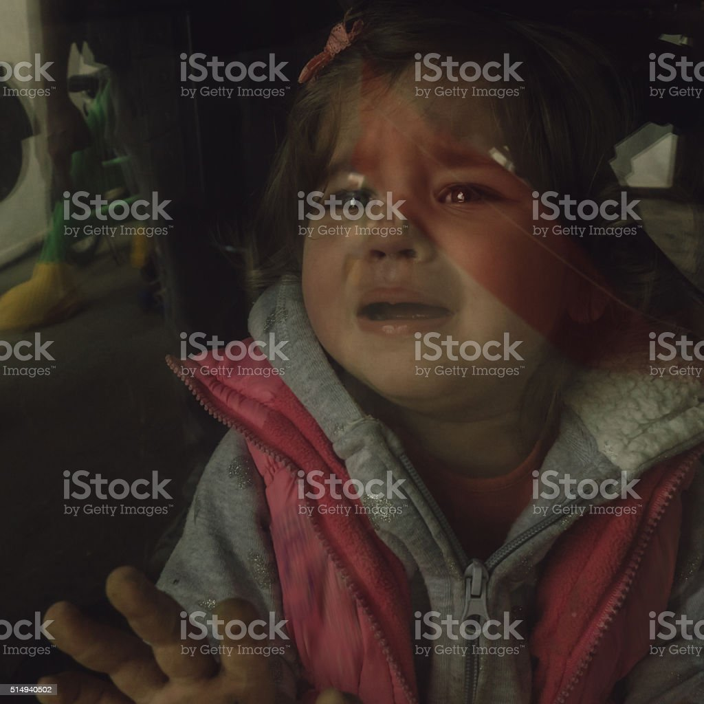 Sad baby girl crying and yelling behind a glass door stock photo