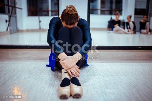Young sad ballerina is sitting on floor in dance class
