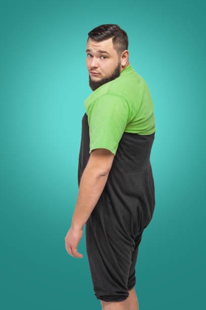sad bearded fat man in black bloomers - pumphose stock-fotos und bilder