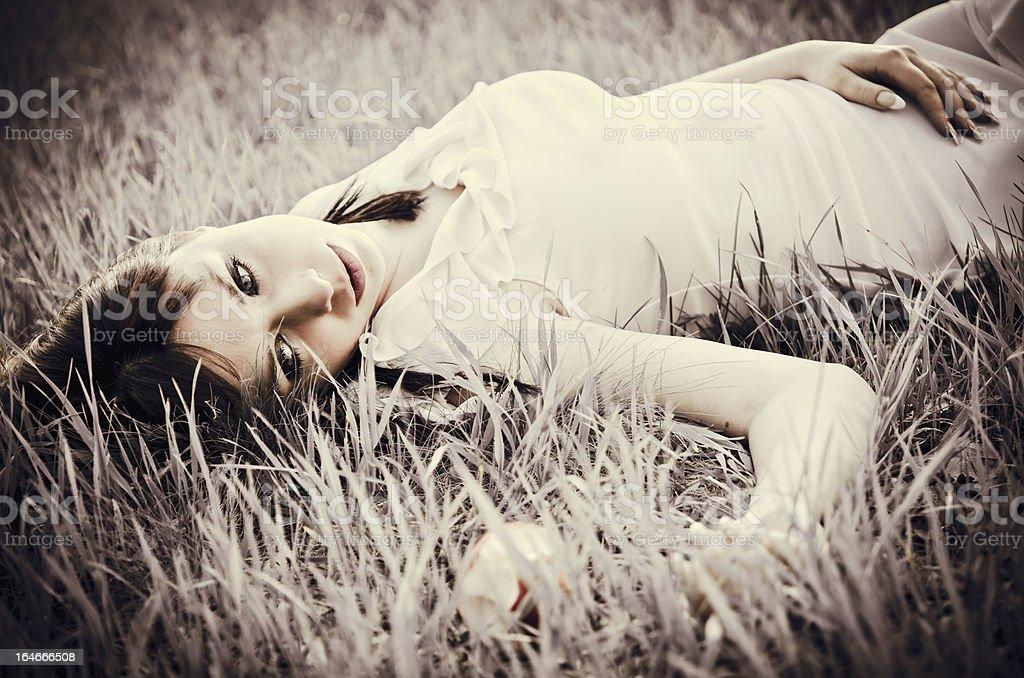 Sad beautiful girl lying on grass. Faded effect royalty-free stock photo