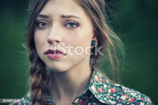 Portrait of a sad young woman with a braid, crying.
