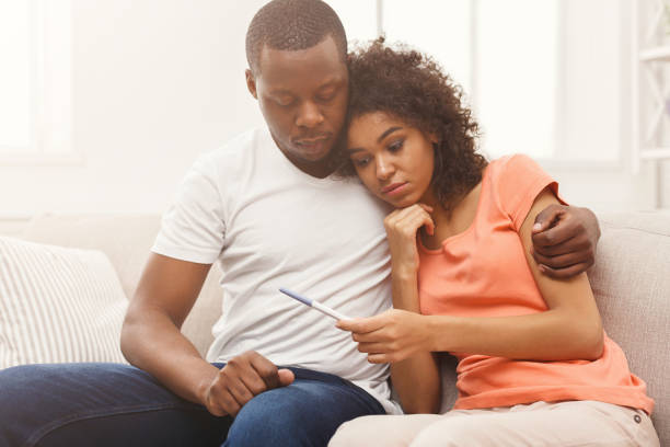 Sad black couple after pregnancy test result Sad african-american couple after negative pregnancy test result, sitting on couch at home, copy space two parents stock pictures, royalty-free photos & images