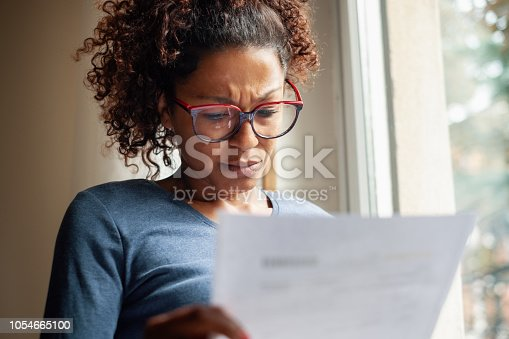 Portrait of worried black woman standing beside window