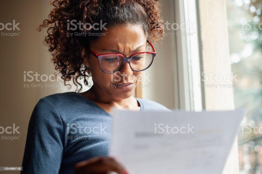 Sad black woman near window reading bad news letter stock photo