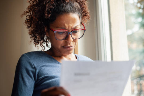 Sad black woman near window reading bad news letter stock photo