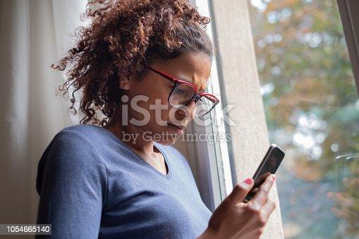 Portrait of doubtful black woman standing beside window sad after ghosting