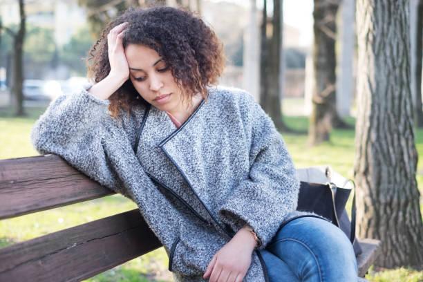 Mulher negra triste sentada sozinho num banco - foto de acervo