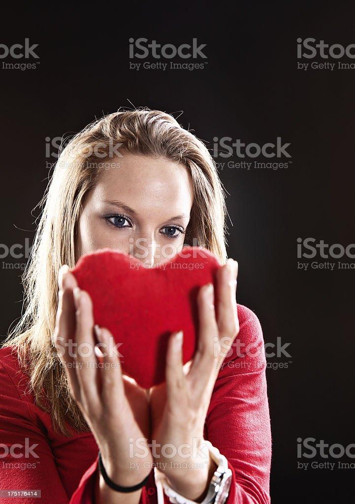 Sad blonde woman holding up red velvet heart stock photo
