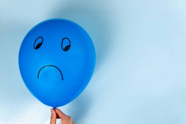 una triste emoticon del blue monday è disegnata su una mongolfiera su sfondo blu. - blue monday foto e immagini stock