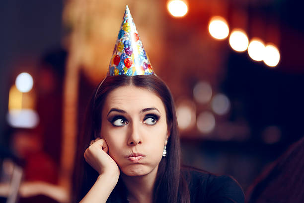 Sad Bored Woman at a Party Having No Fun Portrait of a funny girl with party hat making faces  diva human role stock pictures, royalty-free photos & images