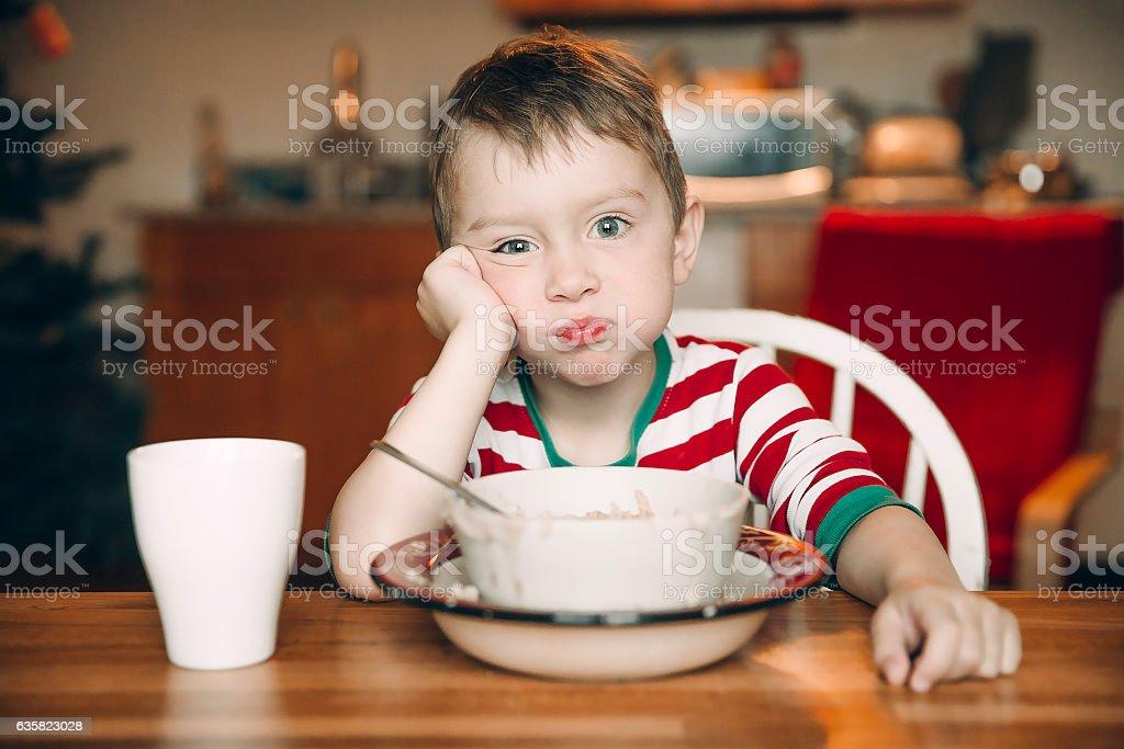 sad boy and a plate of porridge stock photo