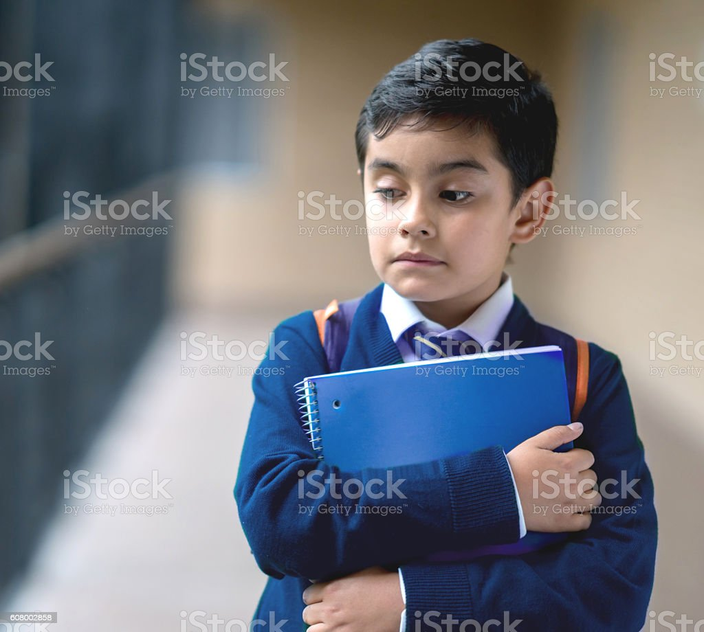 Sad boy at school walking in the hallway holding a notebook -...