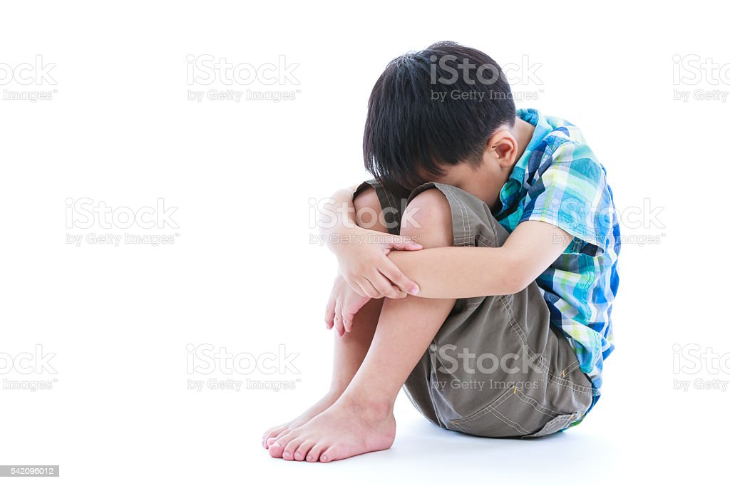 Sad boy barefeet sitting on floor. Isolated on white background. - foto de acervo