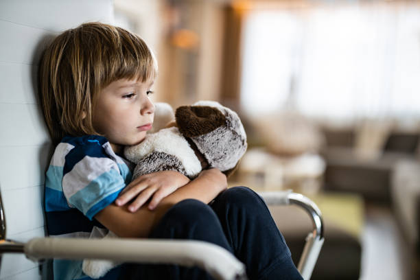 Sad boy embracing his teddy bear in home isolation. stock photo
