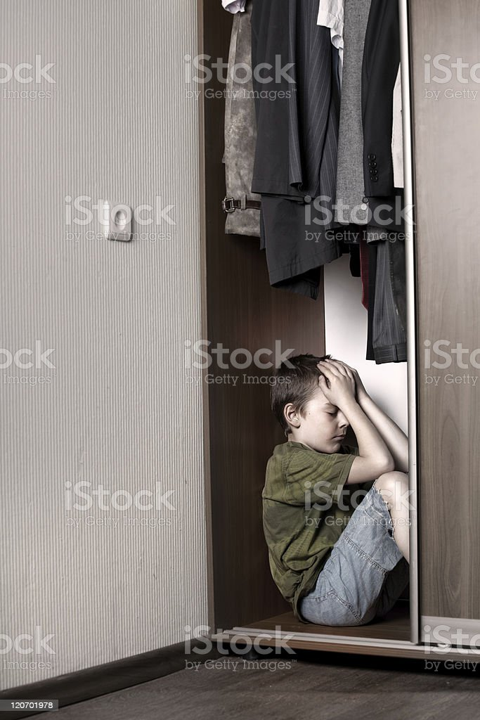 Sad boy, hiding in the closet royalty-free stock photo
