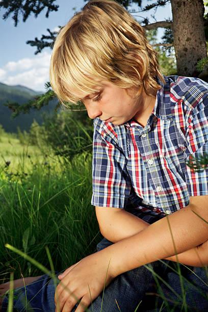 Sad boy in a meadow stock photo