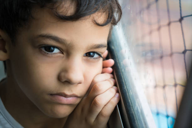 Sad boy looking at camera Child, Boys, Window, People, Indoors poverty stock pictures, royalty-free photos & images
