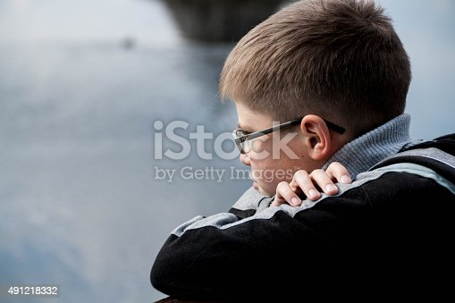 1045032684 istock photo sad boy looking at the river 491218332