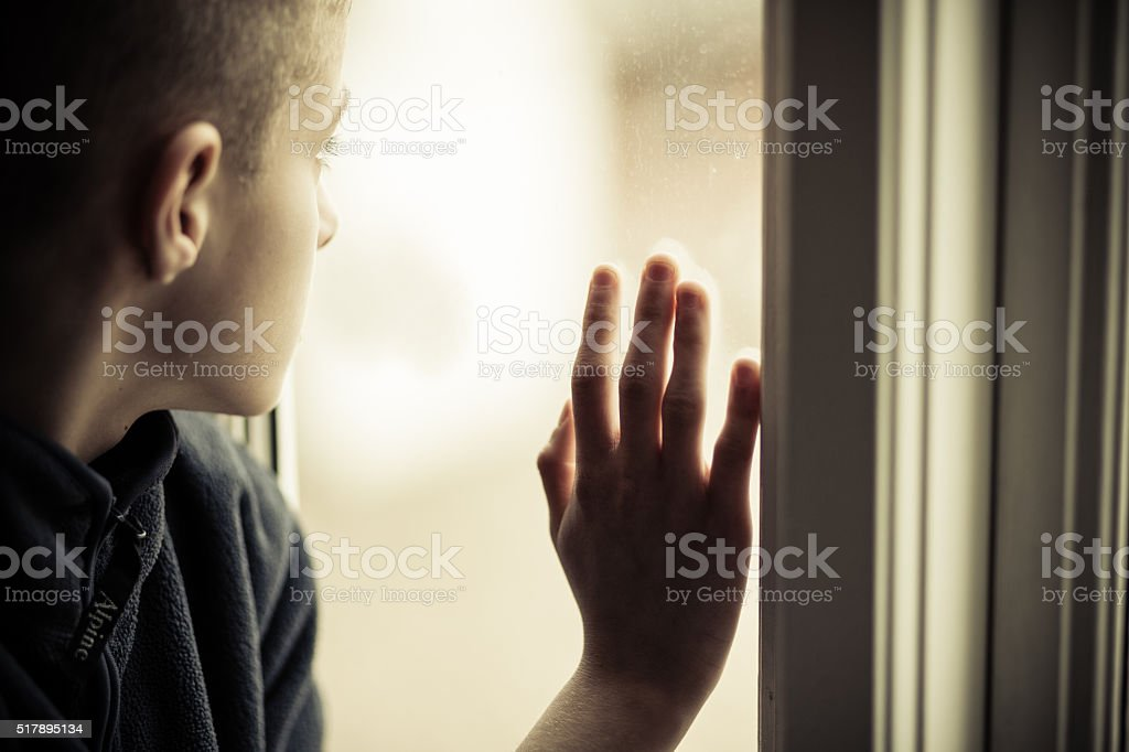 Sad Boy Looking Outside While Holding Glass Window stock photo