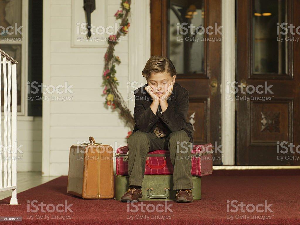 Traurige Junge auf Koffer Lizenzfreies stock-foto