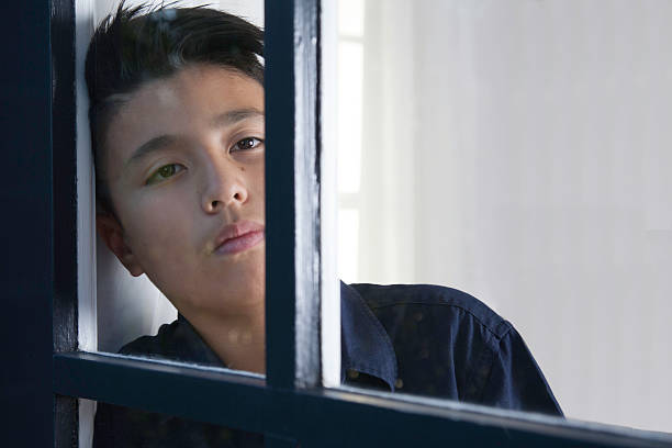 sad boy - boy looking out window stock pictures, royalty-free photos & images