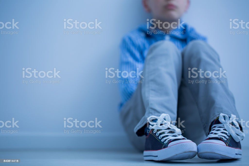 Sad boy sits alone stock photo